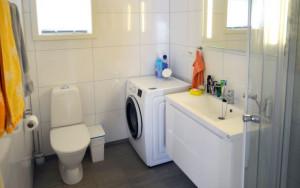 Flislagt bad med toalett, dusj og vaskemaskin.